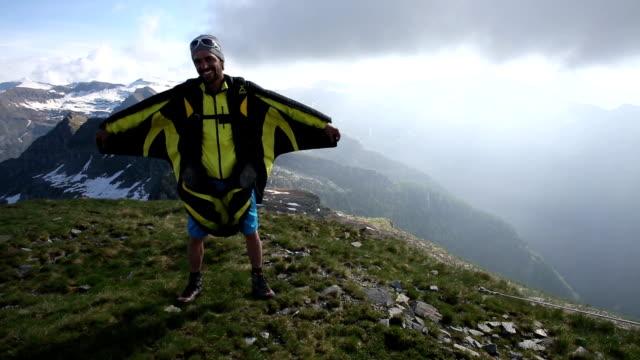 Wingsuit flier poses on mountain summit, spreads wings