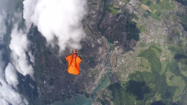 Wingsuit flier soar above Swiss mountains and farmland