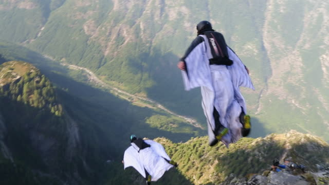 Wingsuit fliers in mid air flight from mountain summit