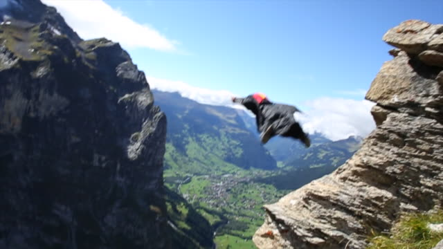 Wingsuit fliers jump from cliff, soars above valley below