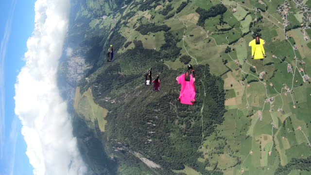 wingsuit fliers soar above mountain landscape - high up stock videos & royalty-free footage