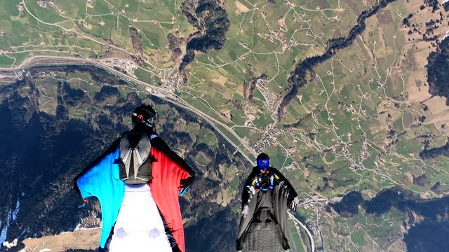 wingsuit fliers soar above swiss mountain landscape - gliding stock videos & royalty-free footage