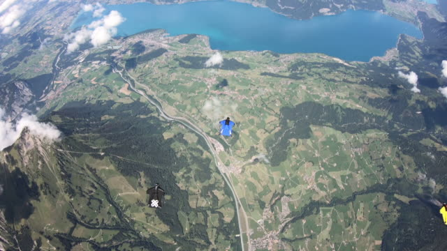 wingsuit fliers soar over mountains and clouds - skydiving stock videos & royalty-free footage