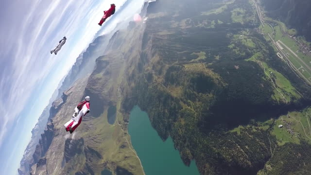 wingsuit fliers soar through tranquil skies above mountain landscape - quartet stock videos & royalty-free footage