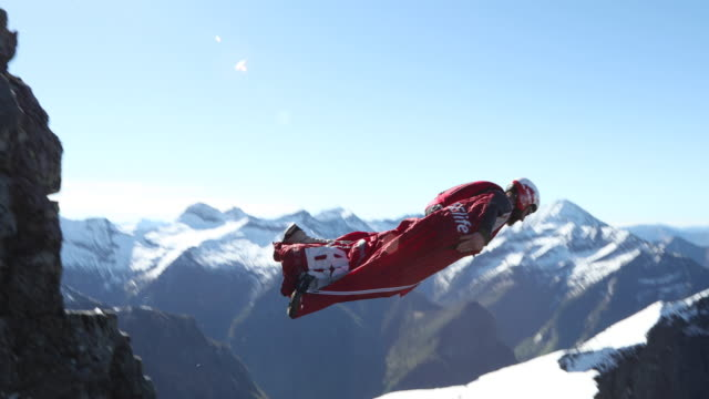 wingsuit flyer jumps from cliff edge, mountains - extreme sports stock videos & royalty-free footage