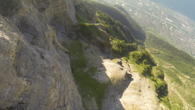 POV wingsuit flying jumping off a cliff and flying close to the rock face