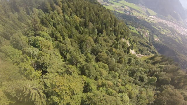 pov wingsuit flying over cliffs and alpine forests - base jumper stock videos & royalty-free footage