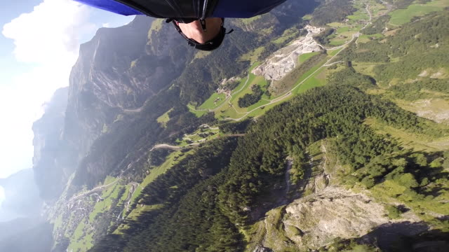 Wingsuit jumping and flying from high mountain cliff