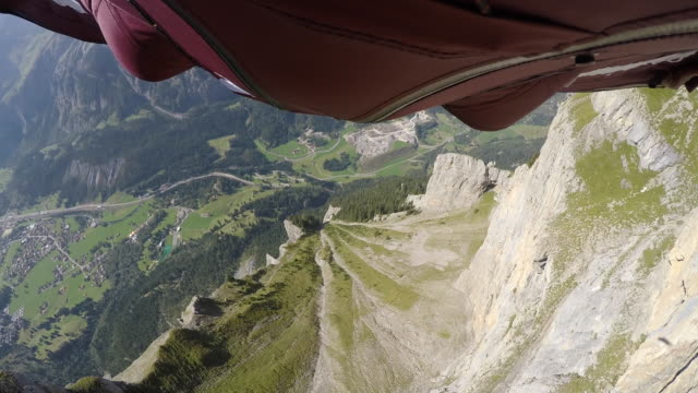 Wingsuit POV jumping off cliff and flying down alpine valley