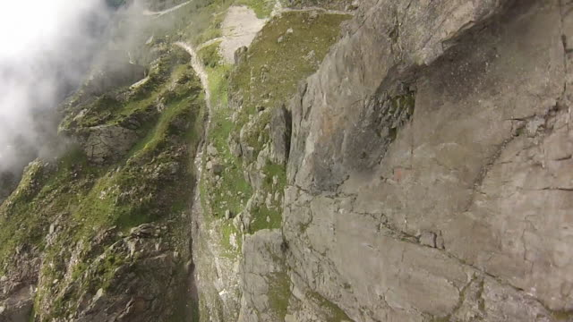 pov wingsuit jumping off cliff and slow motion flying through clouds and over rock spires - cliff stock videos & royalty-free footage