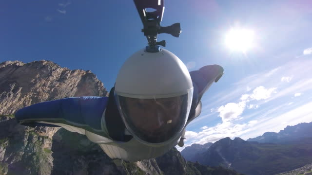 Wingsuit pilot flies over mountains, camera pointed at face