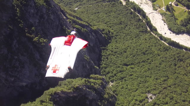 wingsuit pilot flies over mountains, opens parachute - base jumper stock videos & royalty-free footage