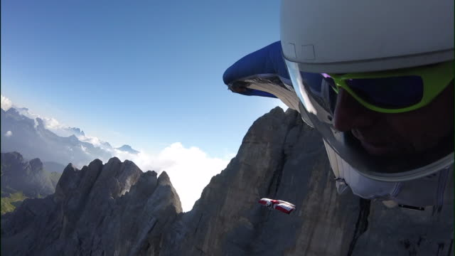 POV of wingsuit pilot flying over mountains and cliffs