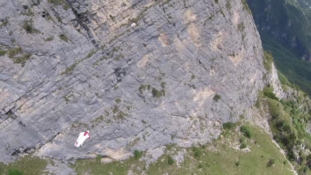 vidéos et rushes de pov de wingsuit pilote volant dans la vallée - danger