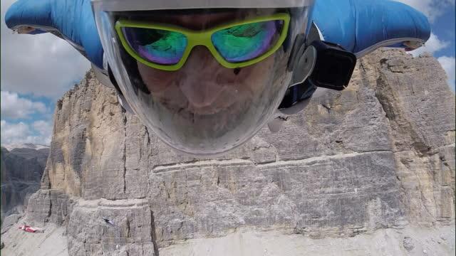 pov of wingsuit pilot flying through valley - trentino alto adige stock videos & royalty-free footage