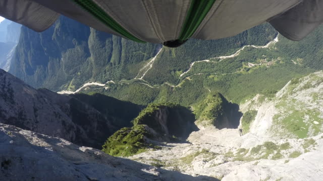POV of wingsuit pilot jumping off rocky cliff