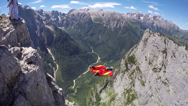Wingsuit pilot jumps off cliff and flies above valley