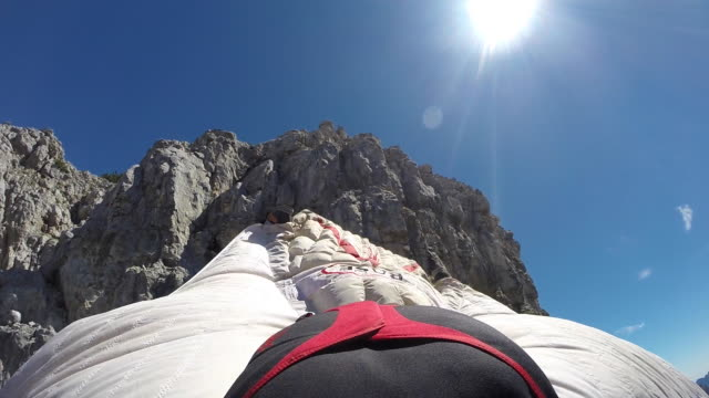 Wingsuit pilot jumps off cliff, camera facing backward