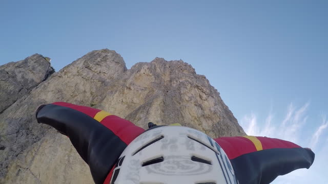 Wingsuit pilot jumps off cliff, camera looking backward