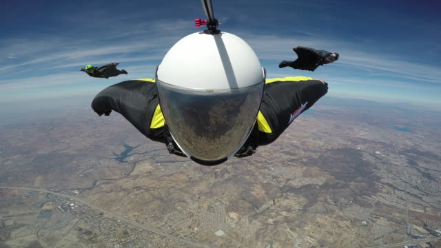 wingsuit pilots fly in formation - air vehicle stock-videos und b-roll-filmmaterial