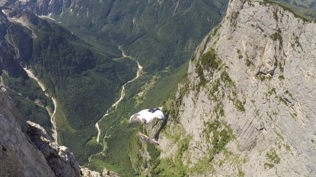 Wingsuit pilots jump off cliff and fly above valley