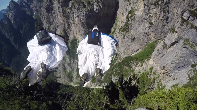 pov of wingsuit pilots jumping - base jumper stock videos & royalty-free footage