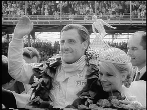 b/w 1966 winner graham hill with wife with tiara at indianapolis 500 / newsreel - paar mittleren alters stock-videos und b-roll-filmmaterial
