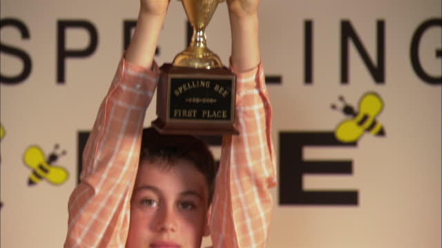 Winner of spelling bee holding trophy above head and smiling at camera / Los Angeles, California