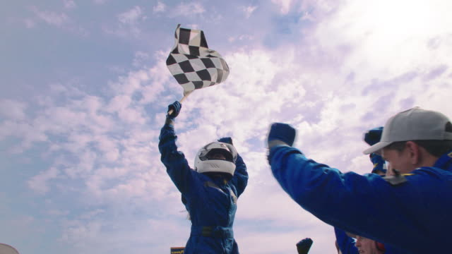 vídeos de stock e filmes b-roll de slo mo. winning race car driver holds up trophy and cheers as blue racing team celebrates victory. - competição