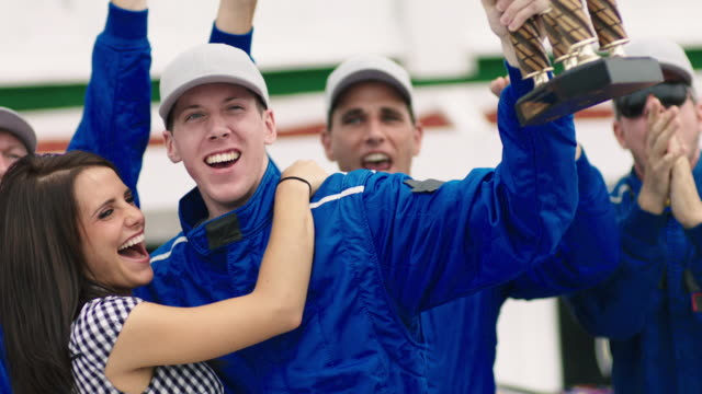 SLO MO. Winning stock car driver holds up trophy and confetti falls as blue racing team celebrates victory.