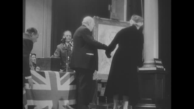 Winston Churchill and Lady Churchill on stage at Westminster Hall step over to portrait / view of portrait / Winston and wife stand and look at...
