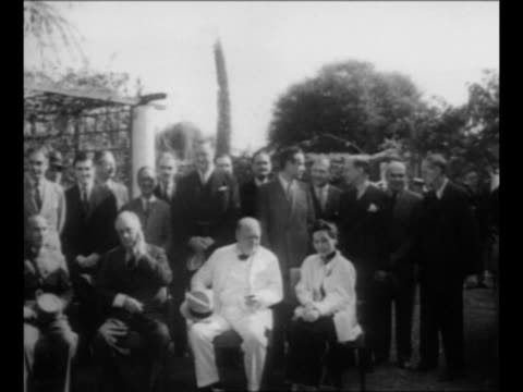 winston churchill stands outdoors in hat, overcoat / chiang kai-shek, franklin d roosevelt, churchill, and madame chiang kai-shek sit in front of... - britisches militär stock-videos und b-roll-filmmaterial