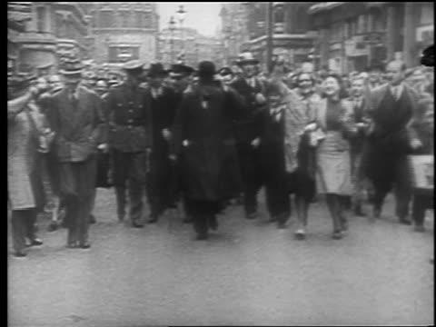 winston churchill walks on street toward camera followed by crowd after london blitz / edu. - 英首相 ウィンストン・チャーチル点の映像素材/bロール