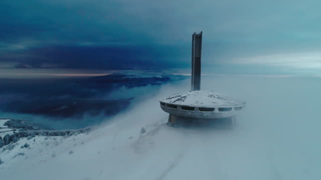 winter aerial view of beautiful, dramatic, fast moving clouds over a snowcapped mountain peak, science fiction mood, buzludzha monument, ufo. - snowcapped mountain stock videos & royalty-free footage