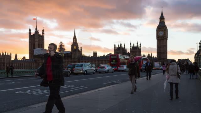 A winter afternoon time lapse of Westminster Palace and Elizabeth Tower (aka, Big Ben) taken from Westminster bridge featuring heavy foot traffic in the foreground and low clouds overhead