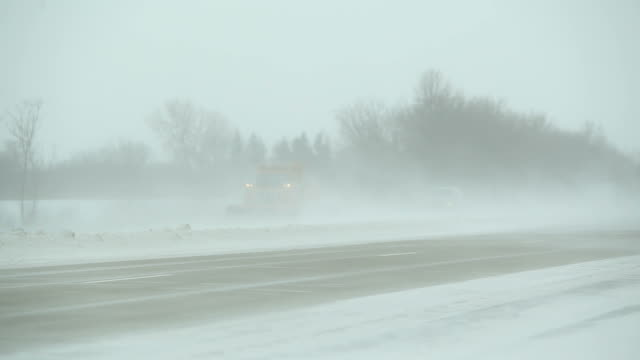 winter blizzard with blowing snow across highway, snowplow and vehicles - plowing stock videos & royalty-free footage