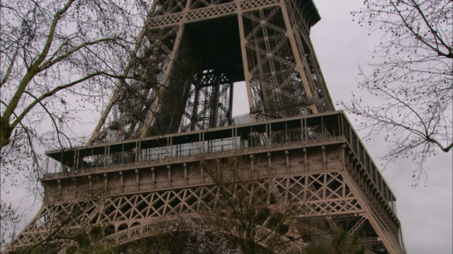 winter branches frame the eiffel tower. - eiffel tower paris stock videos & royalty-free footage