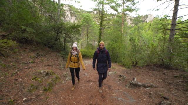 vídeos y material grabado en eventos de stock de winter break of a couple hiking at forest dolly shot - plano de plataforma rodante