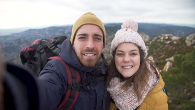 Winter break of young woman and man couple. Taking a selfie in the mountains