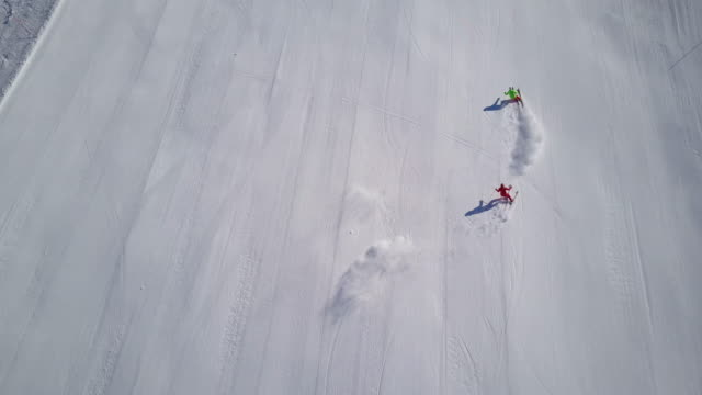 winter breaks, 4k aerial view two skiers followed by drone on empty ski piste - skifahren stock-videos und b-roll-filmmaterial