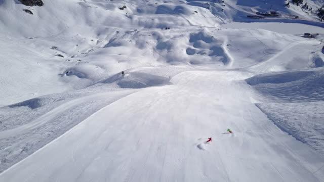 Winter Breaks, 4k aerial view two skiers skiing on wide ski slope