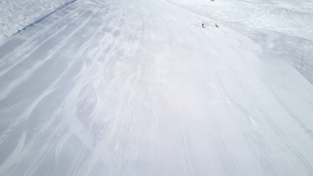 Winter Breaks, aerial view two skiers on wide ski slope