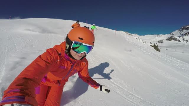 winter breaks, colorful skiers skiing down ski slope - österreich stock-videos und b-roll-filmmaterial