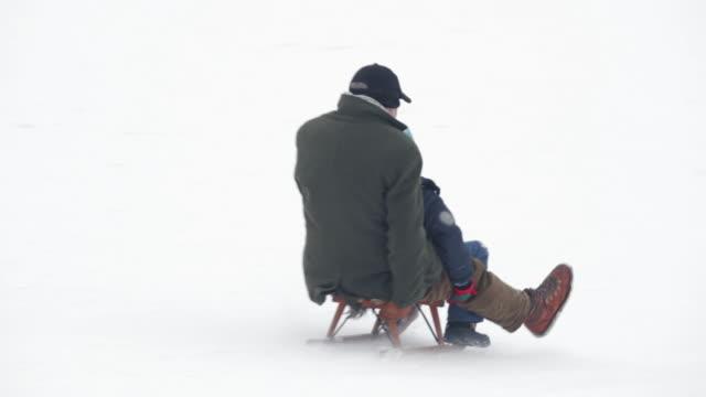 Winter Breaks - Grandfather with grandson sledding