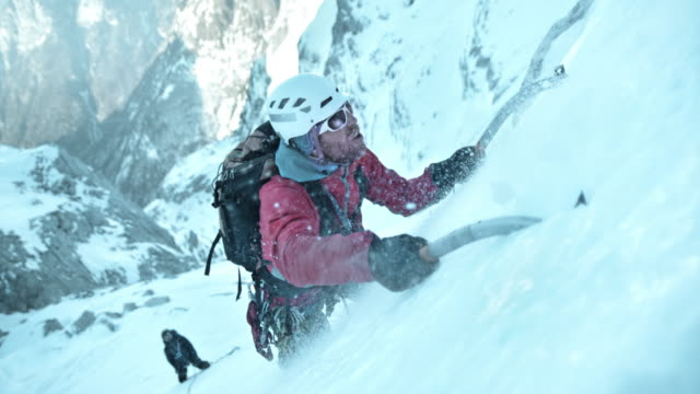 SLO MO winter climber using ice axe to go uphill