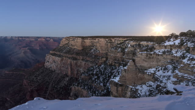 A winter day to night time lapse of the view  from the El Tovar Hotel overlook on the South Rim of the Grand Canyon (Arizona, USA) featuring the moon rising over the horizon with snow covering the ground and dusting the trees.