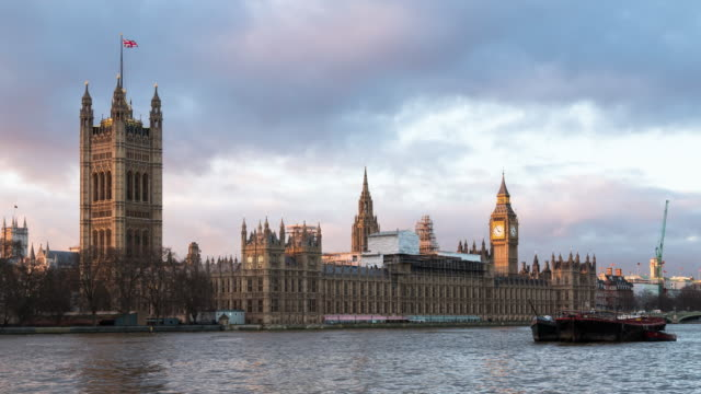 A winter day to twilight time lapse of the Palace of Westminster in London, UK, taken from the south bank of the Thames River featuring heavy clouds moving overhead