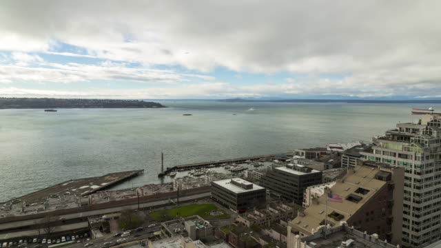 Winter daytime aerial time lapse of low clouds moving perpendicular to high clouds over Elliot Bay (Seattle, WA) with land and sea traffic
