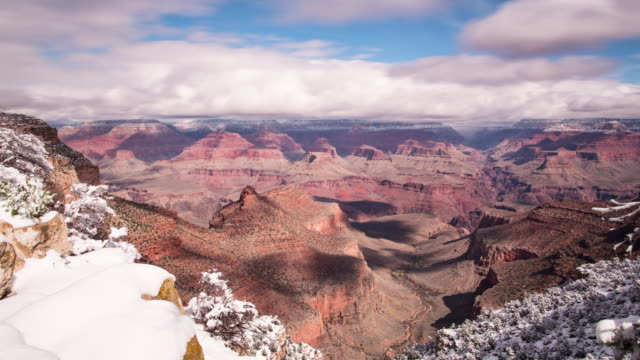 A winter daytime time lapse of the Grand Canyon view from the Bright Angel Lodge overlook on the South Rim of the Grand Canyon (Arizona, USA) the day after a heavy snowstorm, with rapidly moving clouds overhead casting deep shadows on the canyon floor bel
