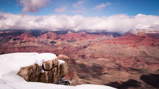 A winter daytime time lapse of the Grand Canyon view from Yaki Point on the South Rim of the Grand Canyon (Arizona, USA) the day after a heavy snowstorm, with clouds moving overhead casting deep shadows on the canyon floor below.